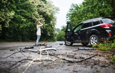 Young woman standing by the damaged car after a car accident.