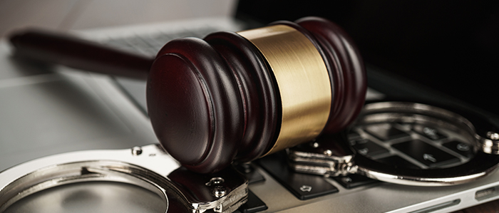 handcuffs and judge gavel on computer